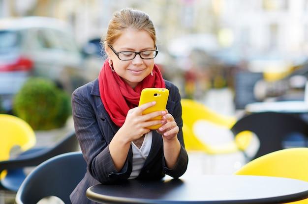 La giovane donna sta usando lo smartphone nella caffetteria