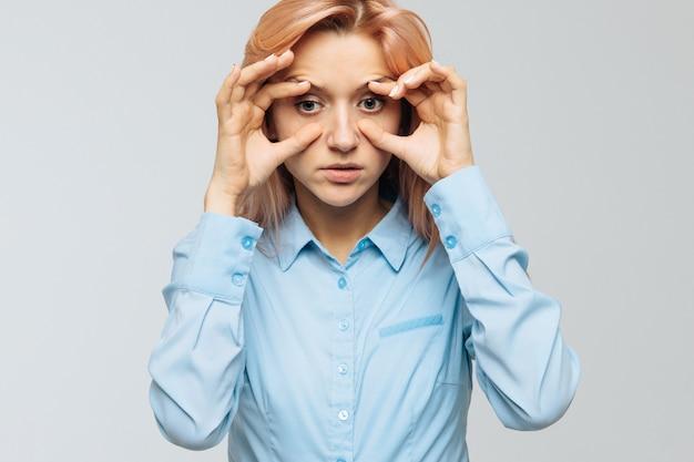 La giovane donna stanca in camicia blu vuole dormire al lavoro o all'università