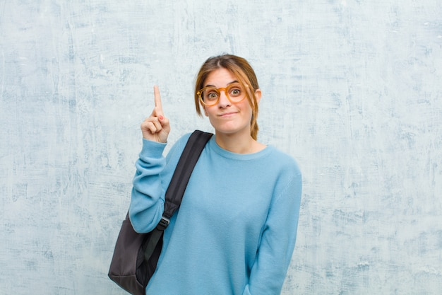 La giovane donna studentessa si sente come un genio che tiene orgogliosamente il dito in aria dopo aver realizzato una grande idea, dicendo eureka contro il muro del grunge
