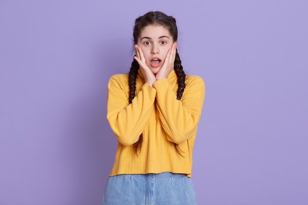 La giovane donna stupita tiene i palmi delle mani sulle guance, guarda la telecamera con grandi occhi e la bocca aperta