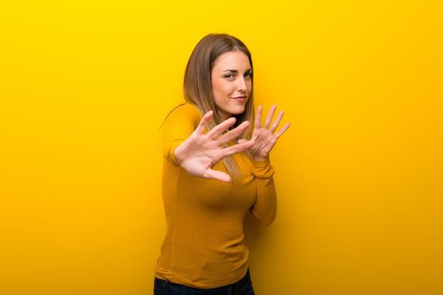 La giovane donna su sfondo giallo è un po 'nervosa e spaventata allungando le mani verso la parte anteriore