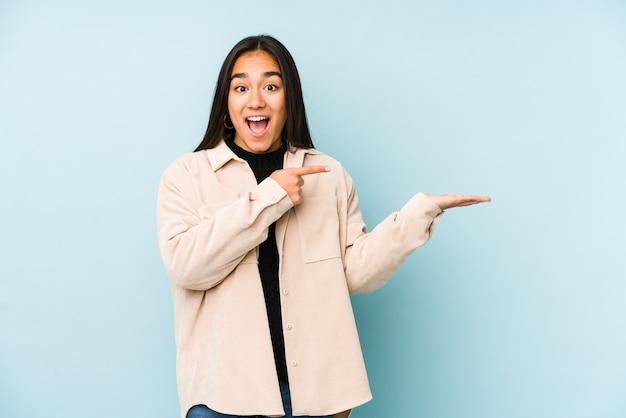La giovane donna su una parete blu ha eccitato tenendo uno spazio in bianco sulla palma.