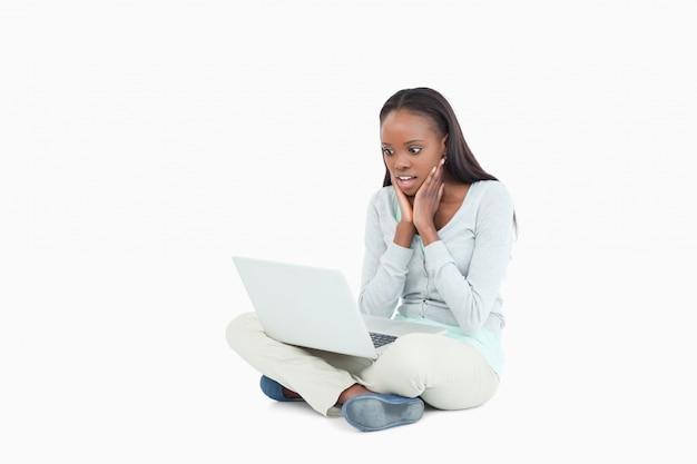 La giovane donna sul pavimento non può credere a cosa sia sul suo schermo