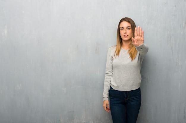 La giovane donna sulla parete strutturata che fa il gesto di arresto che nega una situazione che pensa sbagliato