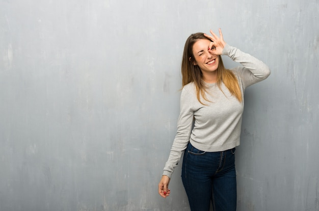 La giovane donna sulla parete strutturata fa l'emozione faccia buffa e pazza