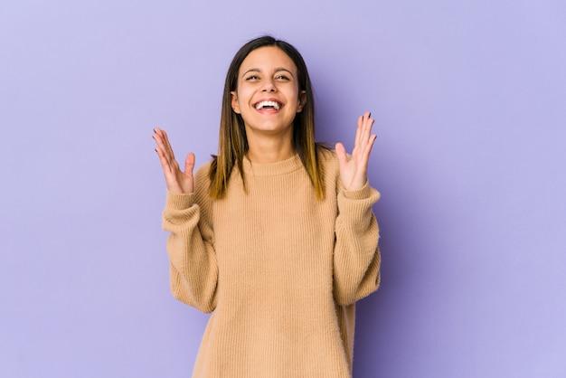 La giovane donna sulla parete viola ride ad alta voce