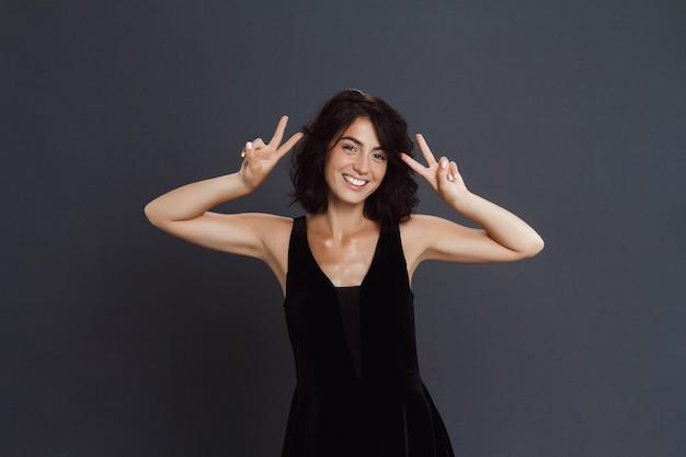 La giovane donna sveglia che posa sopra la parete grigia e fa un gesto divertente di due pace