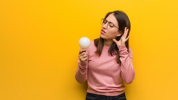 La giovane donna sveglia che tiene una lampadina prova ad ascoltare un gossip