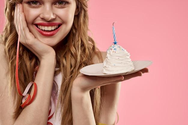 La giovane donna sveglia con un bigné e le candele celebra il compleanno, lo studio, parete rosa