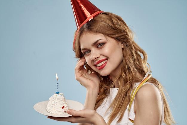 La giovane donna sveglia con un bigné e le candele celebra il compleanno, lo studio, spazio blu