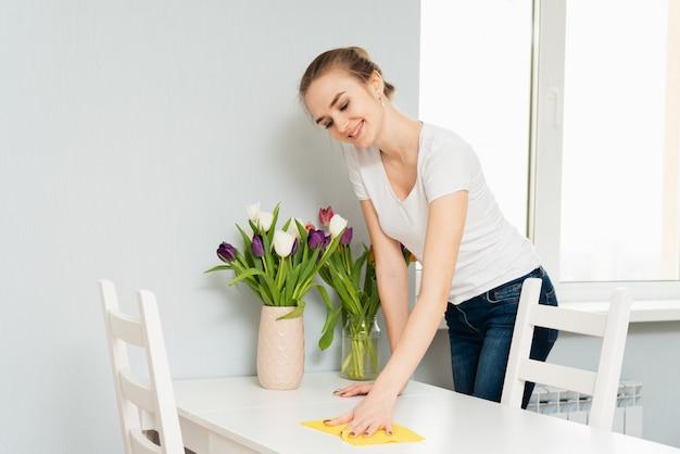 La giovane donna sveglia sorride mentre pulisce la sua casa e fa la pulizia bagnata. faccende domestiche