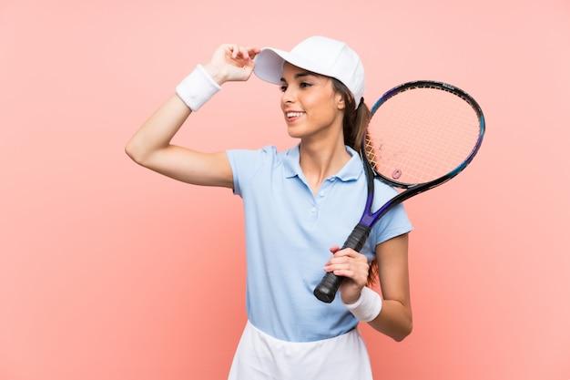 La giovane donna tennista sopra un muro rosa isolato ha realizzato qualcosa e intendendo la soluzione