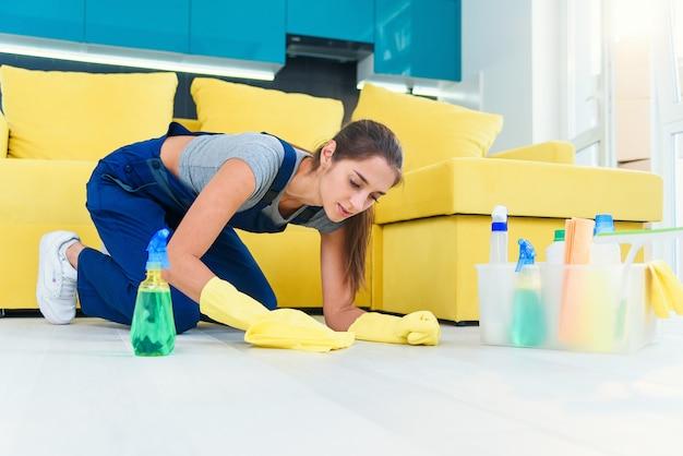 La giovane donna vestita in abiti speciali si trova in ginocchio e pulisce il parquet in legno con detergenti e straccio sulla cucina moderna.