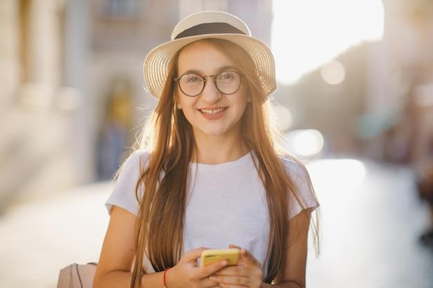 La giovane donna viaggia in cappello e occhiali si trova sulla strada della città e sms sms sul suo telefono cellulare.