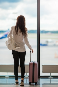 La giovane donna vicino alla grande finestra panoramica in un salotto dell'aeroporto che aspetta arriva