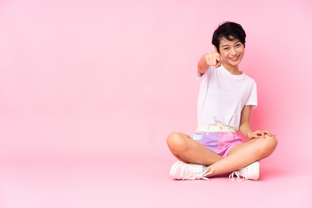 La giovane donna vietnamita con i capelli corti che si siede sul pavimento sopra la parete rosa isolata indica il dito con un'espressione sicura