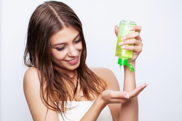 La giovane e bella donna applica balsamo sui capelli danneggiati per ripristinare e prendersi cura dei capelli