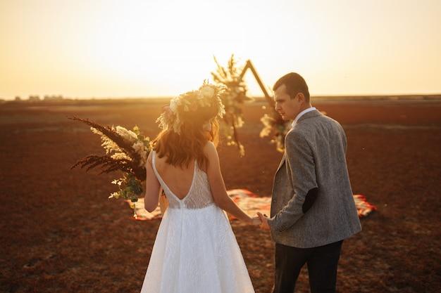 La giovane e bella sposa e lo sposo si divertono. giorno del matrimonio in stile boho.