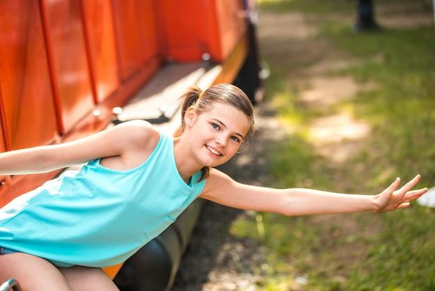 La giovane e donna felice che tira affronta la porta del treno che cerca qualcuno alla stazione ferroviaria