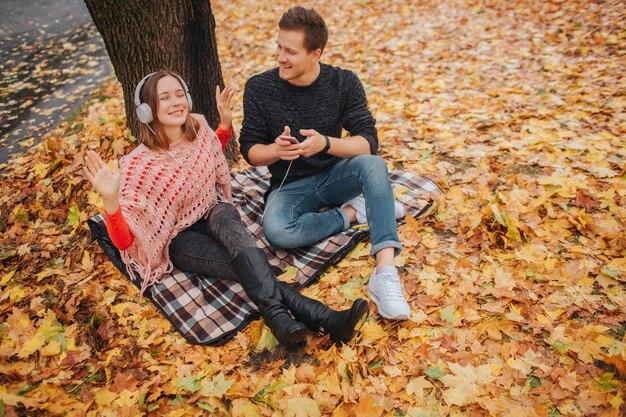 La giovane e giovane donna positiva ama ascoltare la musica attraverso le cuffie. lei si siede sulla coperta. guy è oltre a lei. tiene il telefono e guarda la donna.