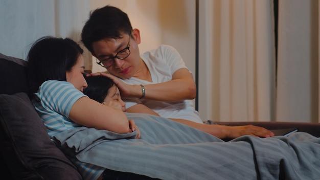 La giovane famiglia asiatica ha letto le fiabe alla figlia a casa. la madre giapponese felice, il padre si rilassa con la bambina si gode il tempo di buona qualità sdraiato sul letto prima di andare a dormire in camera da letto a casa di notte.