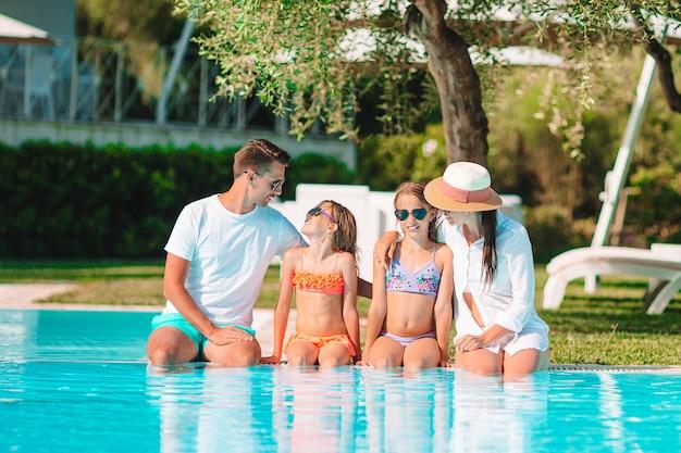 La giovane famiglia con due bambini gode delle vacanze estive nella piscina all'aperto