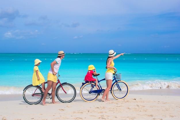La giovane famiglia con i bambini guida le bici su una spiaggia esotica tropicale