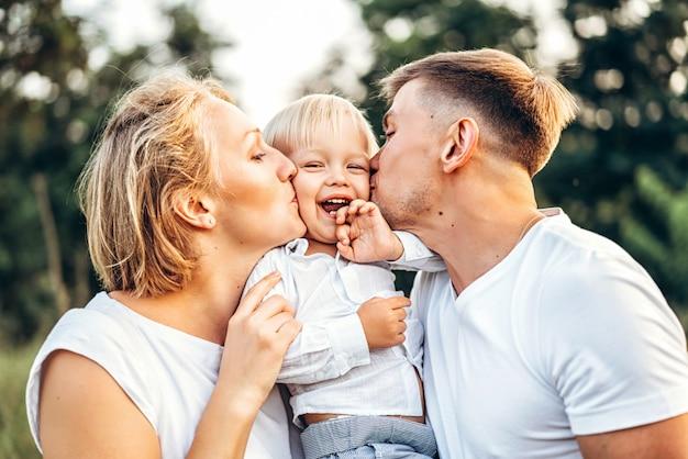 La giovane famiglia con il piccolo figlio si diverte all'aperto