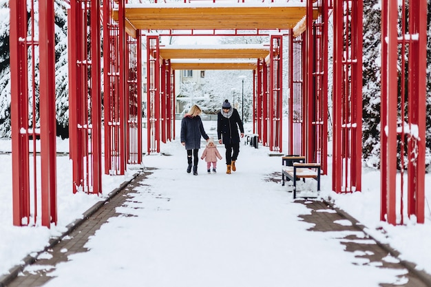 La giovane famiglia felice cammina con il bambino sulla via dell'inverno, mamma, papà, bambino