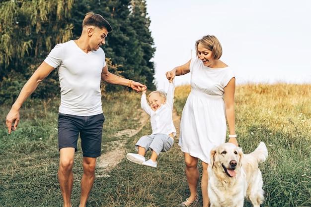 La giovane famiglia felice con il cane si diverte all'aperto