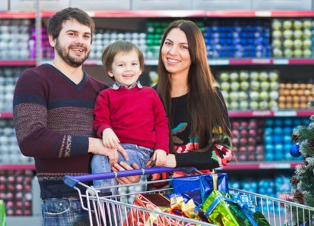 La giovane famiglia felice nel supermercato sceglie i regali per i christmass