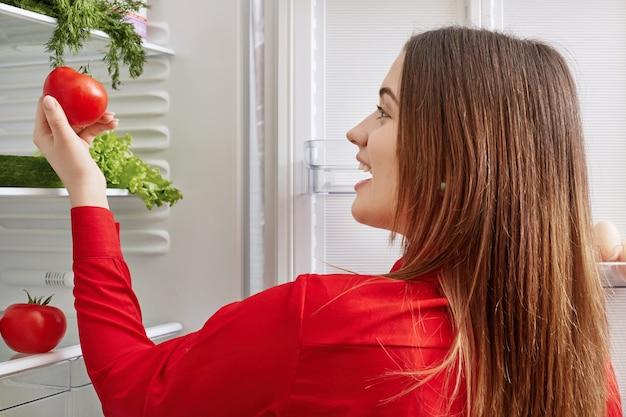 La giovane femmina allegra felice di vedere i pomodori in frigorifero, andando a fare l'insalata di verdure, continua a dieta