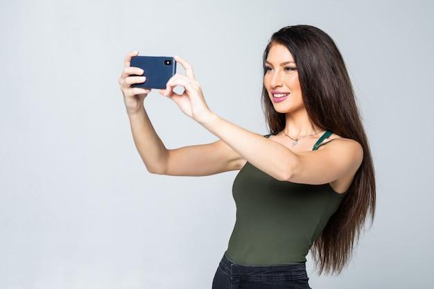 La giovane femmina attraente felice in vestito prende le foto usando il suo telefono cellulare, spara