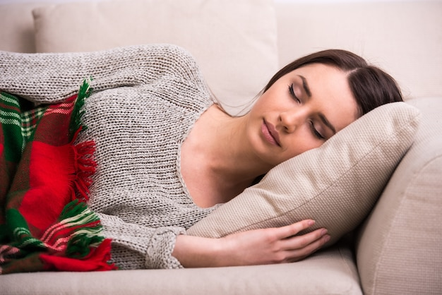 La giovane femmina attraente sta dormendo sul sofà a casa.