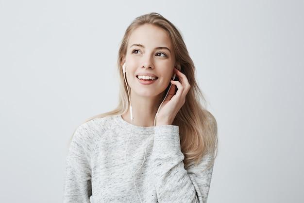 La giovane femmina caucasica felice espressiva indossa i capelli tinti biondi sciolti, ascolta musica in cuffia, gode di piacevoli melodie, ha buon umore.