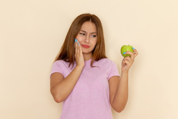 La giovane femmina di vista frontale in maglietta rosa e blue jeans ha ferito i suoi denti che mordono la mela su grey