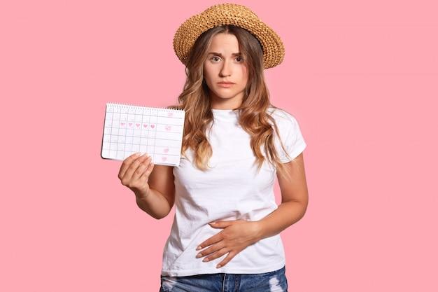 La giovane femmina europea dispiaciuta sente dolore e spasmo durante il periodo mestruale, tiene il calendario, tiene le mani sul fondo della pancia, indossa un cappello di paglia e una maglietta bianca, isolata sopra il muro rosa.