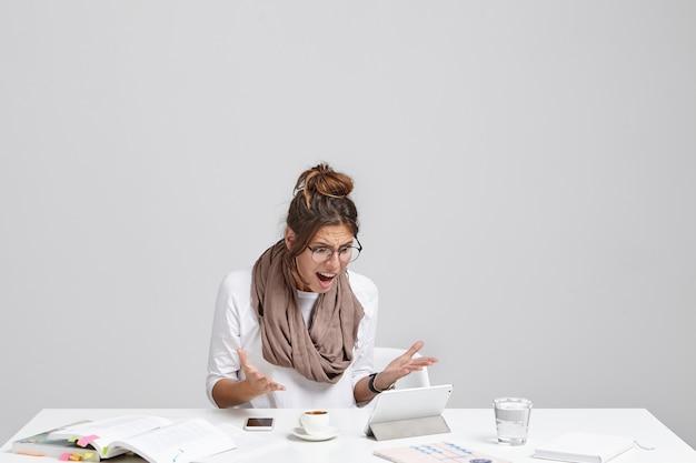 La giovane femmina fastidiosa e preoccupata ha problemi durante il lavoro, non sa come usare il programma sul tablet