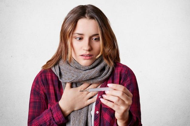 La giovane femmina frustrata ha sintomi di influenza, alta temperatura, mal di testa e mal di gola, guarda con espressione scioccata al termometro