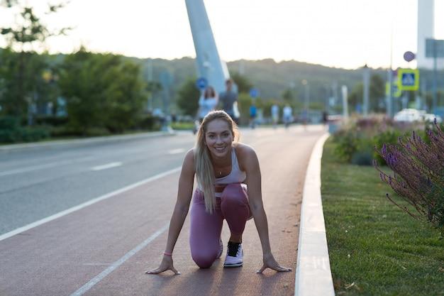 La giovane femmina in abiti sportivi corre giù il parco all'aperto della pista