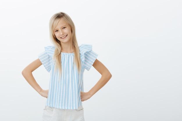 La giovane figlia adorabile vuole aiutare la mamma in cucina. tiro al coperto di fiduciosa ragazza alla moda con i capelli biondi, tenendo le mani sui fianchi con un sorriso sicuro di sé, in piedi sopra il muro grigio