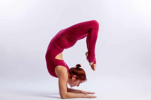 La giovane ginnasta atletica della donna in tuta relativa alla ginnastica fa l'allungamento nelle pose difficili