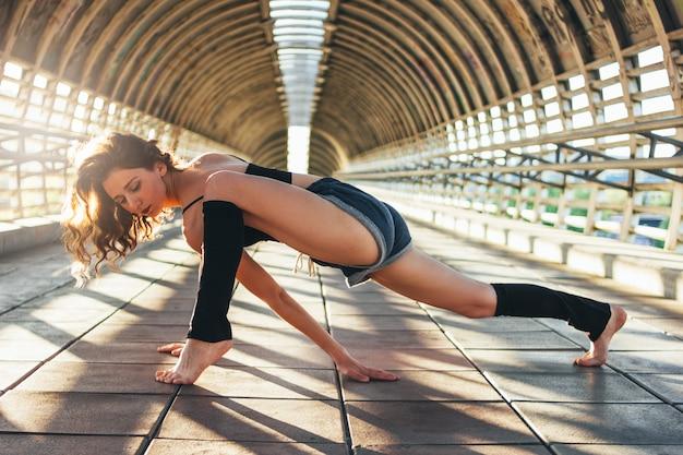 La giovane ginnasta snella del ballerino di via della donna castana si siede nella posa delle spaccature sul ponte della via