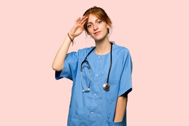 La giovane infermiera della testarossa che saluta con consegna il fondo rosa