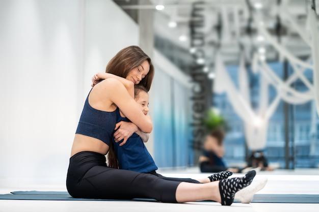 La giovane madre adulta abbraccia la sua piccola figlia in palestra