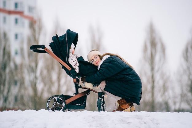 La giovane madre alla moda abbraccia sua figlia che si siede in passeggino nel parco all'aperto all'inverno.