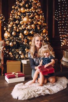 La giovane madre bionda e la sua piccola figlia in bianco hanno tricottato i vestiti che aprono un regalo di natale vicino ad un albero di natale in salone accogliente nell'inverno