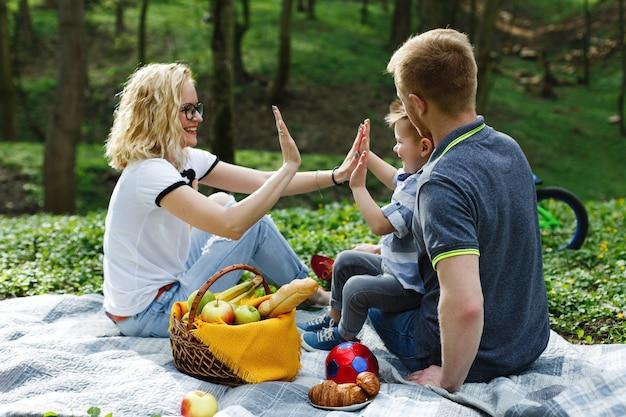La giovane madre bionda gioca con suo figlio durante il picnic nel parco