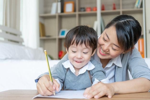 La giovane madre che insegna a suo figlio scrive su carta con amore
