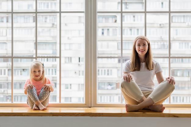 La giovane madre che si siede con sua figlia di 3 anni nel loto posa il asana sul davanzale della finestra davanti alla finestra